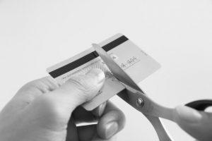 クレジットカードをハサミで切ってる人