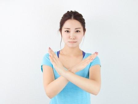 バツ印をしている女性
